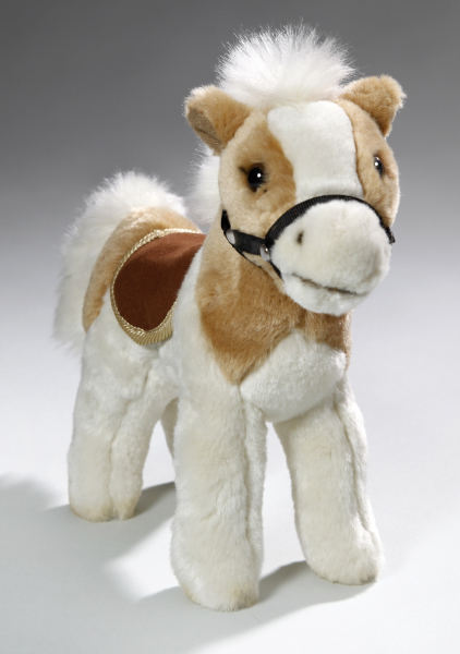 Horse standing beige-white with saddle